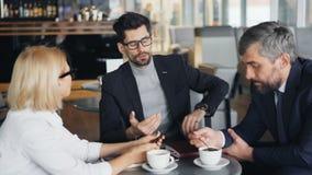 Empresario hermoso que habla con los hombres de negocios acertados en café moderno metrajes