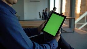 Empresario hisp?nico que sostiene una tableta negra con la pantalla verde ningunas caras almacen de metraje de vídeo