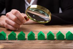Empresario Holding Magnifying Glass sobre modelo de la casa fotos de archivo