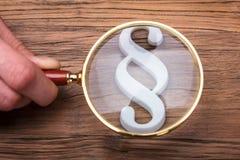 Empresario Holding Magnifying Glass sobre símbolo del párrafo imagenes de archivo