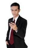 Empresario joven que comprueba en el email en el teléfono, aislado en pizca Foto de archivo libre de regalías