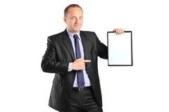 Empresario joven que señala a un sujetapapeles Foto de archivo libre de regalías