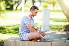 Empresario joven que trabaja en el parque afuera en banco de madera Hombre que usa el ordenador portátil, escribiendo el texto Op fotografía de archivo libre de regalías