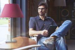 Empresario joven que trabaja en inicio en oficina moderna usando la tableta digital Sirva los vidrios que llevan y los vaqueros,  fotografía de archivo libre de regalías