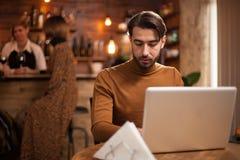 Empresario joven que trabaja en su ordenador portátil en una cafetería imagenes de archivo