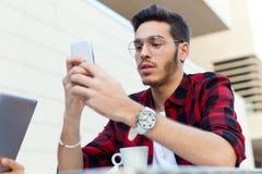 Empresario joven que usa su teléfono móvil en la cafetería foto de archivo