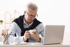 Empresario mayor que come resto, café de consumición y trabajando en el ordenador portátil fotografía de archivo libre de regalías