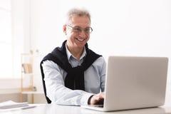 Empresario mayor que trabaja en el ordenador portátil en casa imagenes de archivo