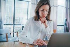 Empresario pensativo de sexo femenino usando el ordenador port?til m?vil para mirar una nueva soluci?n del negocio durante proces imagen de archivo libre de regalías