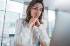 Empresario positivo de sexo femenino usando el ordenador port?til m?vil para mirar una nueva soluci?n del negocio durante proceso fotos de archivo