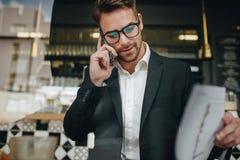 Empresario que habla en el teléfono celular que mira los papeles de la oficina en a fotografía de archivo libre de regalías