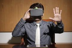 Empresario que lleva las auriculares de la realidad virtual imagenes de archivo