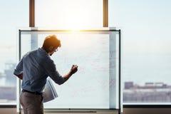 Empresario que pone sus ideas del negocio en whiteboard en boardro fotografía de archivo