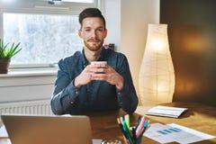 Empresario que se sienta en su oficina imagen de archivo