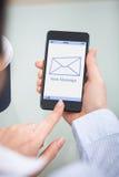 Empresario que sostiene el teléfono móvil con la nueva muestra del mensaje imagen de archivo