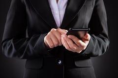 Empresario que sostiene el teléfono móvil negro sobre fondo negro fotos de archivo libres de regalías