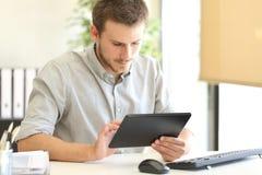 Empresario que trabaja en línea con una tableta imagen de archivo