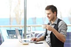 Empresario que trabaja en línea en una cafetería imagenes de archivo