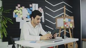 Empresario que trabaja en la tableta digital con el documento de los datos del gráfico en la oficina almacen de metraje de vídeo