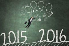 Empresario que vuela para alcanzar los números 2016 Imagenes de archivo