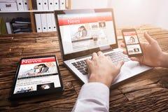 Empresario Reading Online News en el ordenador portátil imagen de archivo