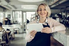 empresario Rubio-cabelludo que debe el restaurante que sostiene poca tableta blanca imagen de archivo libre de regalías