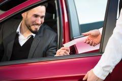 Empresario Sitting Inside Car de Giving Receipt To del ayudante de cámara imagen de archivo libre de regalías