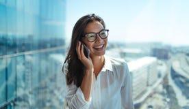 Empresario sonriente de la mujer que habla sobre el teléfono fotos de archivo