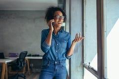 Empresario sonriente de la mujer que habla sobre el tel?fono imagenes de archivo