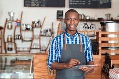 Empresario sonriente que se coloca en su café usando una tableta digital Imágenes de archivo libres de regalías