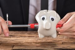 Empresario Squeezing Piggy Bank en herramienta de la abrazadera en el escritorio imágenes de archivo libres de regalías