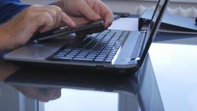 Empresario Working en oficina usando Smartphone y la conexión inalámbrica del ordenador portátil foto de archivo