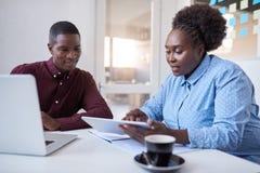 Empresarios africanos jovenes que usan la tecnología junta en una oficina Foto de archivo libre de regalías