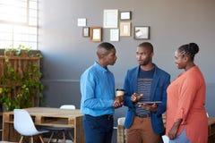 Empresarios africanos que discuten flujo de trabajo digital en una oficina Fotos de archivo