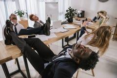 empresarios agotados que duermen en sala de conferencias con los pies fotos de archivo libres de regalías