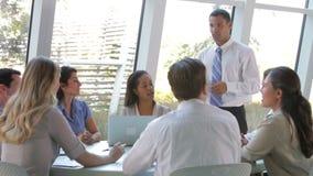 Empresarios asentados alrededor de la tabla que tiene reunión metrajes