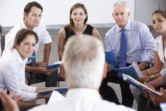 Empresarios asentados en círculo en el seminario de la compañía Imagen de archivo libre de regalías