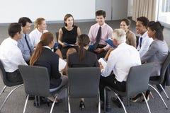 Empresarios asentados en círculo en el seminario de la compañía Foto de archivo