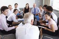 Empresarios asentados en círculo en el seminario de la compañía Fotografía de archivo libre de regalías