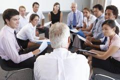 Empresarios asentados en círculo en el seminario de la compañía Fotos de archivo