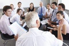 Empresarios asentados en círculo en el seminario de la compañía imágenes de archivo libres de regalías
