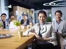 Empresarios asiáticos jovenes que se encuentran en oficina Fotos de archivo libres de regalías