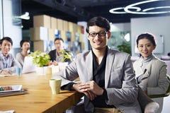 Empresarios asiáticos jovenes que se encuentran en oficina Fotos de archivo