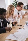 empresarios cansados que comen los tallarines en sala de conferencias fotos de archivo