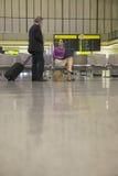 Empresarios con el ordenador portátil y el equipaje en pasillo del aeropuerto imagen de archivo