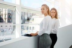 Empresarios confiados de las mujeres jovenes que esperan comenzar de la conferencia mientras que se colocan en interior moderno d fotos de archivo