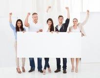 Empresarios confiados que sostienen la cartelera en blanco Foto de archivo