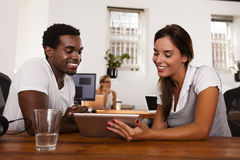 Empresarios de lanzamiento que discuten una tableta Imagen de archivo libre de regalías