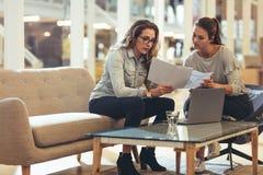 Empresarios de las mujeres que discuten el trabajo en oficina imagen de archivo libre de regalías
