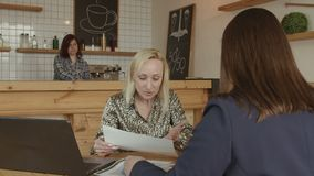 Empresarios de sexo femenino que discuten en el encuentro en café almacen de video